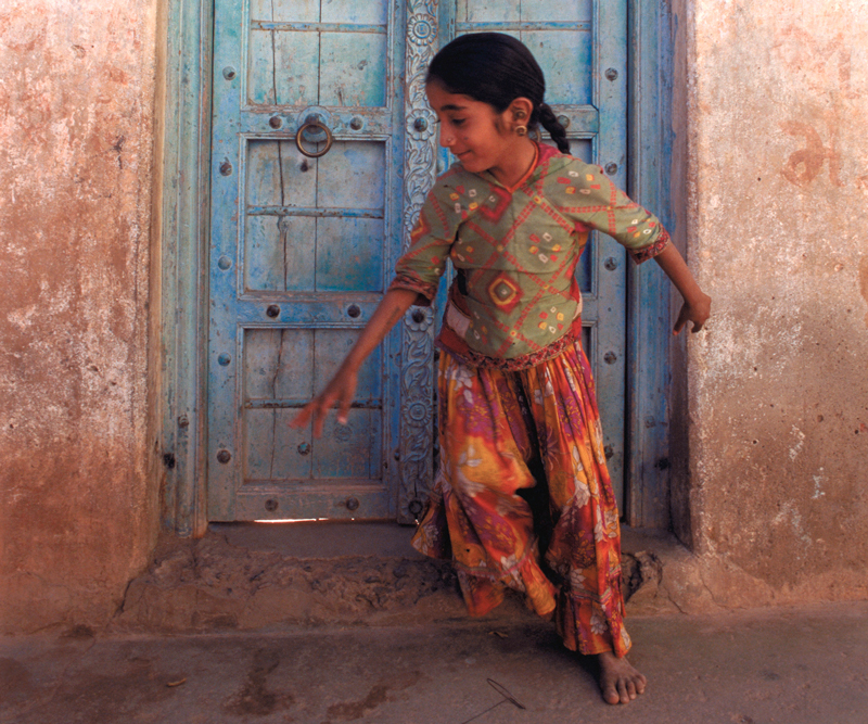 Girl playing in doorway in India
